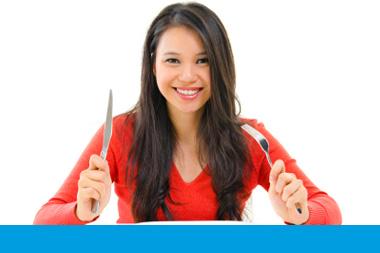 Mujer con cuchillo y tenedor a punto de comer una receta
